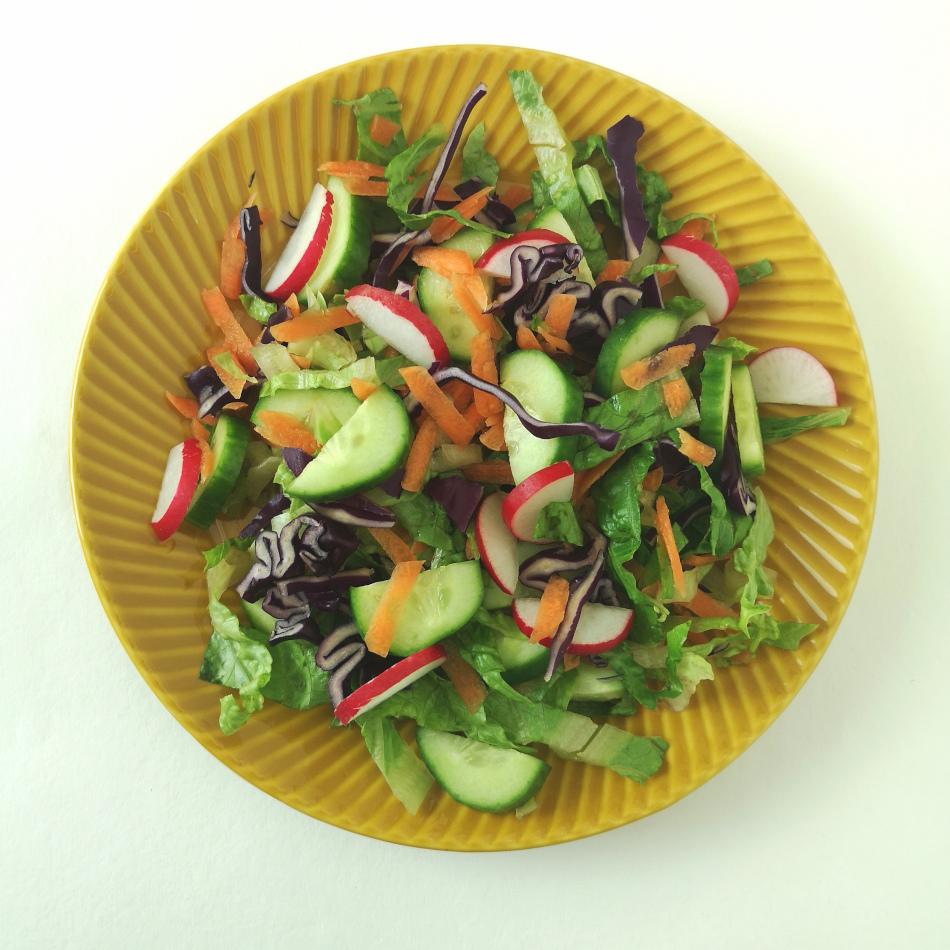 En sallad bestående av sallat, gurka, rödkål. rädisor och riven morot på ett gult fat.