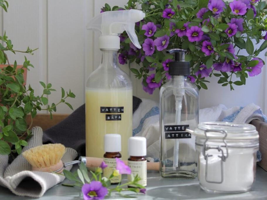 flaskor och burkar med såpa, ättika och bikarbonat att använda som mer naturliga städprodukter